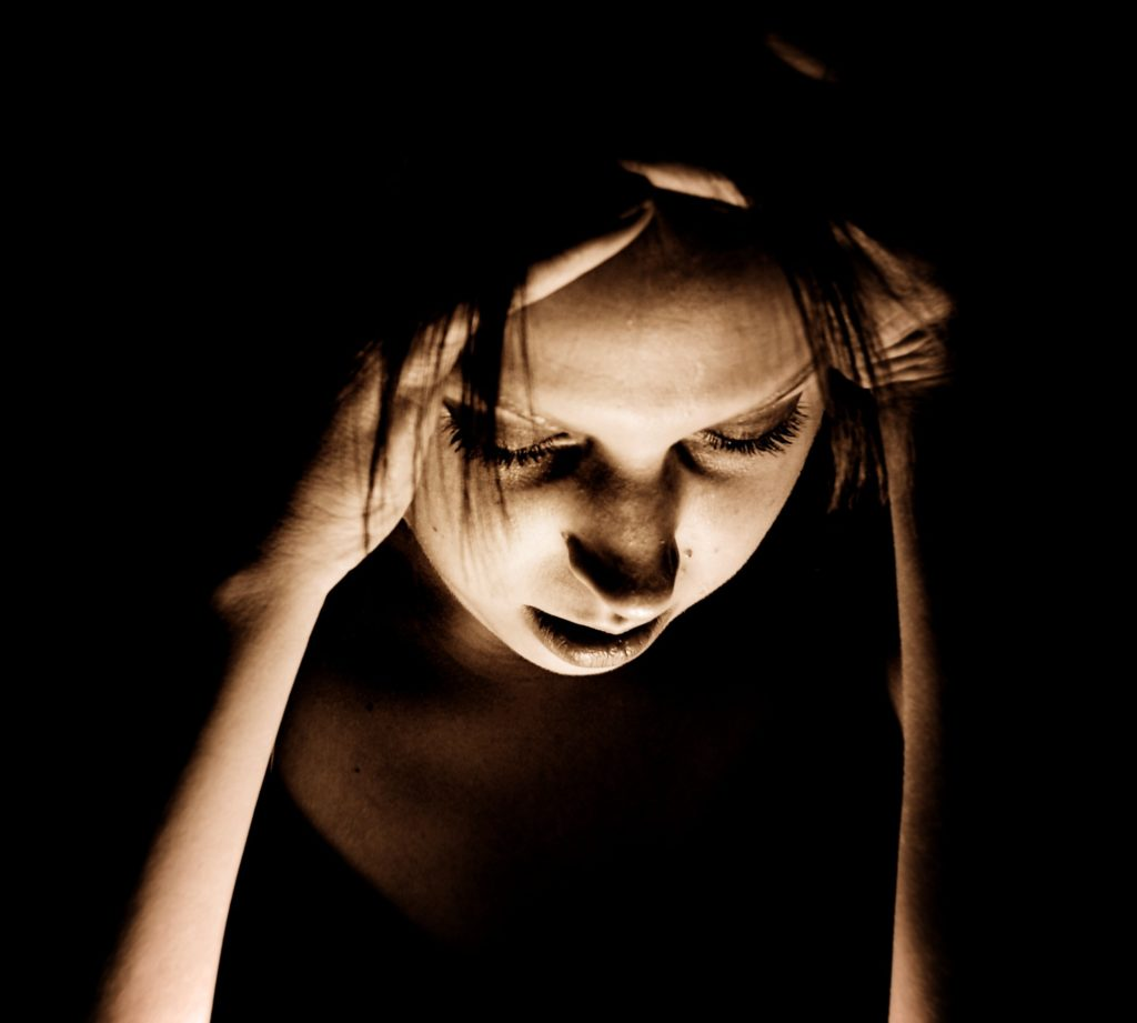 Woman suffering from a migraine in a dark room.